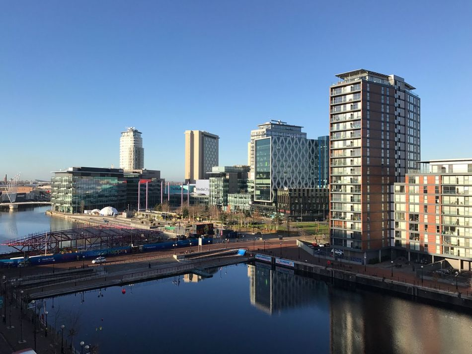 This is Salford Quays. Architecture Building Exterior City Built Structure Water Reflection River Skyscraper Clear Sky Modern Bridge - Man Made Structure Waterfront Outdoors City Life No People Day Urban Skyline Cityscape Nature Sky Salford Quays Mediacityuk EyeEm Gallery Fresh On Eyeem  City Life