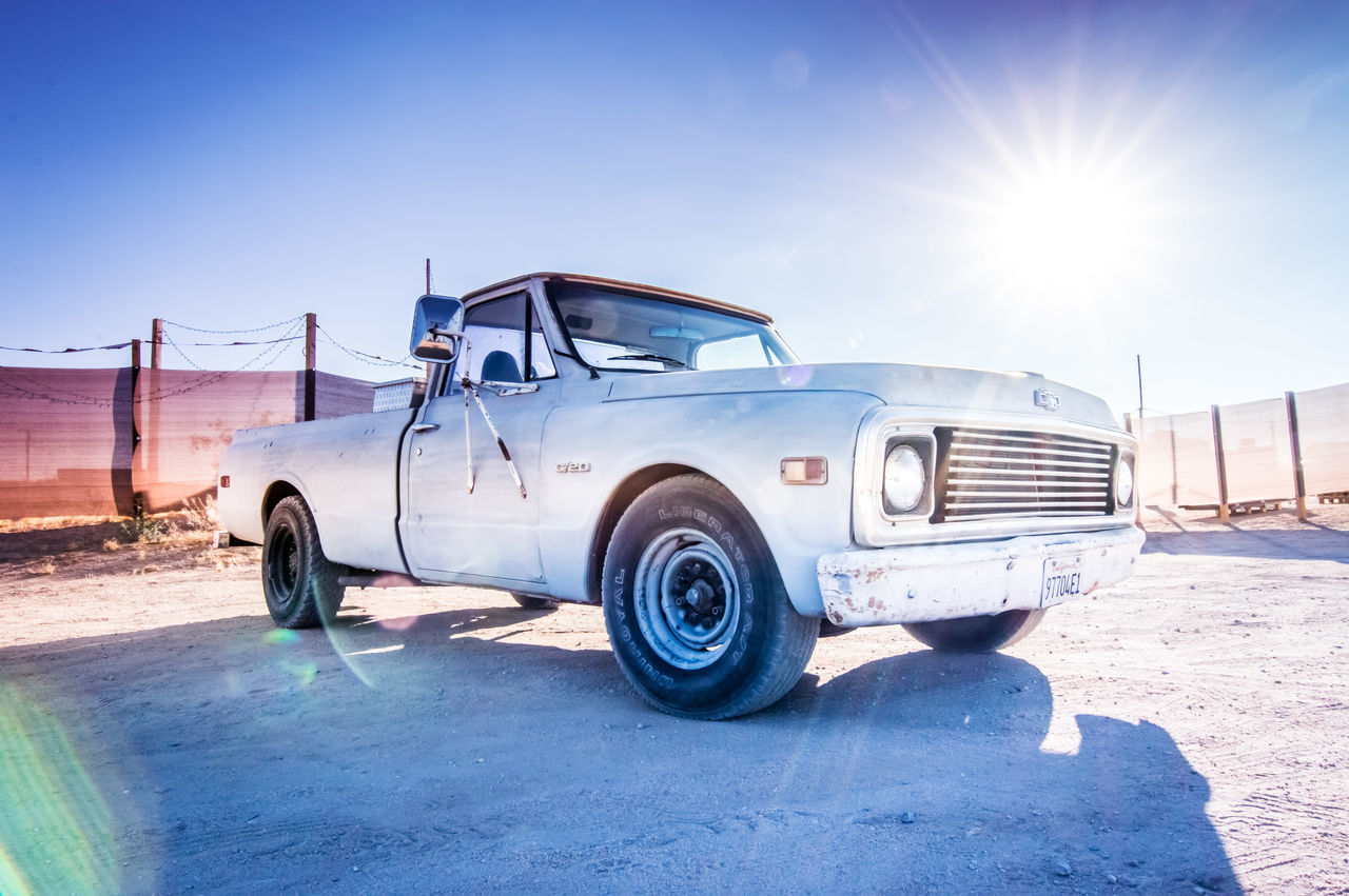 sunlight, sunny, transportation, lens flare, stationary, blue, land vehicle, day, clear sky, outdoors, old-fashioned, no people, shadow, sky, architecture
