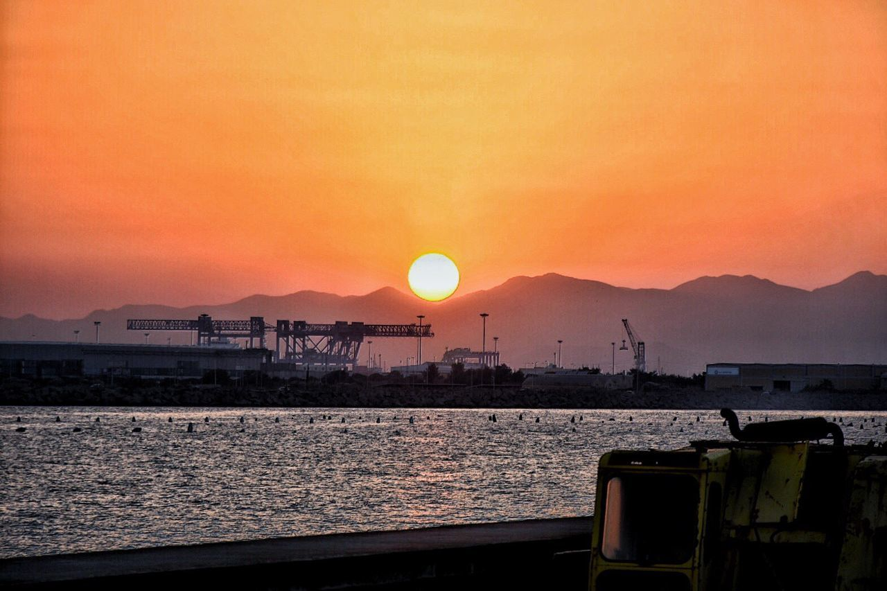 Sunset Sun Water Mountain Scenics Crane - Construction Machinery Orange Color Sea Commercial Dock Mountain Range Beauty In Nature Harbor Travel Destinations Idyllic Tranquil Scene Tranquility Sky Majestic Freight Transportation Development Cagliari, Sardinia Outdoors Cagliari Urban City