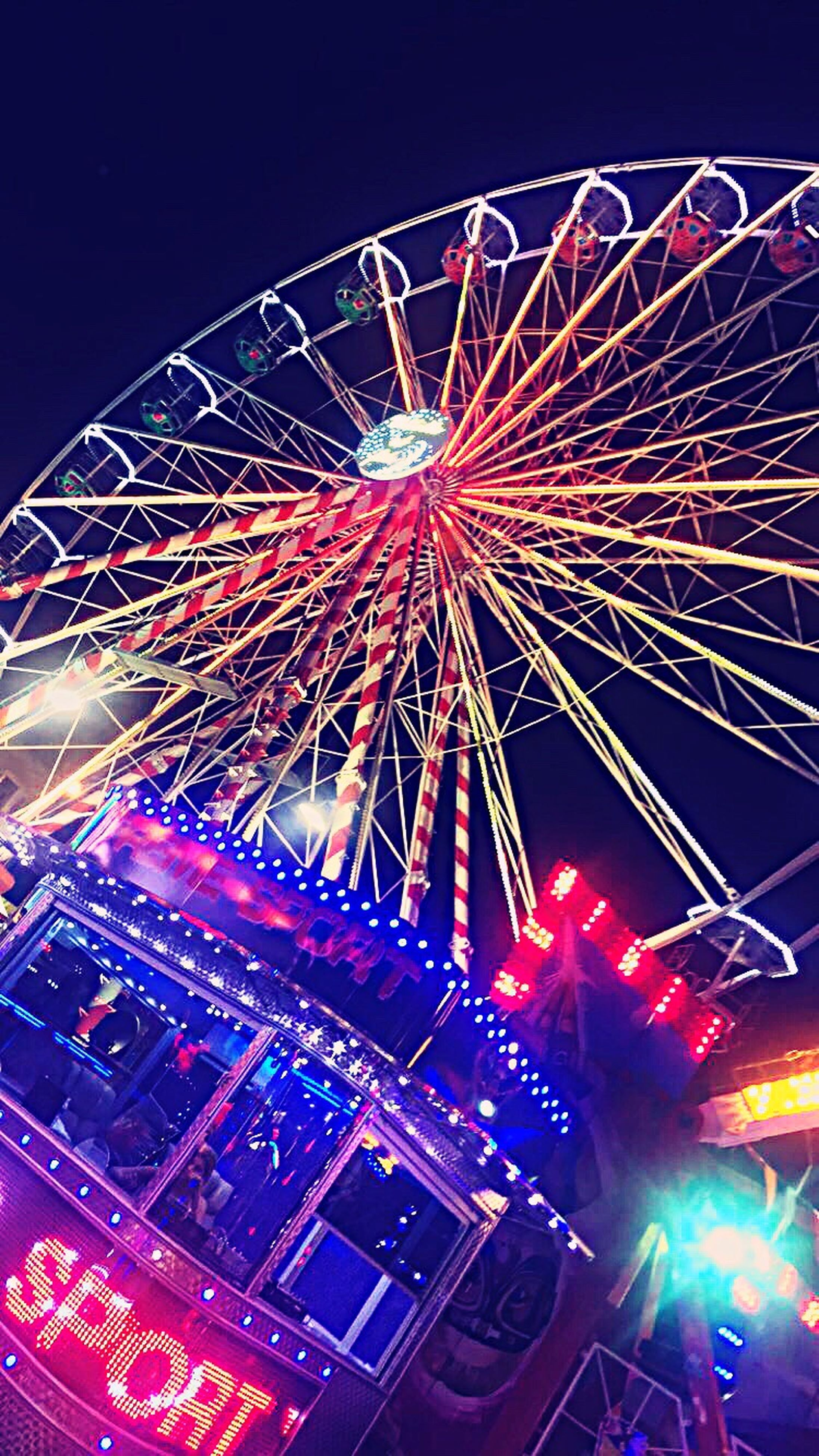 arts culture and entertainment, low angle view, night, illuminated, amusement park, amusement park ride, multi colored, motion, ferris wheel, sky, fun, travel destinations, dark, enjoyment, tourism, exploding, outdoors, colorful, bright, entertainment, nightlife, vacations, traveling carnival, no people, atmosphere, event