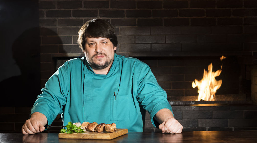 Chef with meat cooked on a skewer on the background of a brazier with an open fire Adult Background Brazier Caucasian Chef Cooked Fire Flame Food Food And Drink Front View Man Mature Adult Meat Men Mid Adult Night One Man Only One Mature Man Only One Person Only Men Open Plate Portrait Skewer