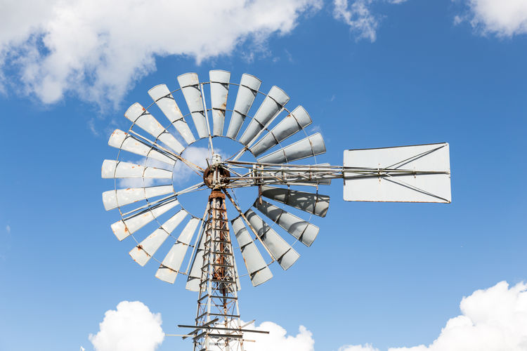 wind-powered water pump against partly cloudy sky Aermotor Tourist Attraction  Alternative Energy Blue Day Engineering Low Angle View Metal Mill Nature No People Outdoors Sky Technology Traditional Windmill Water Pump Wind Power Wind Turbine Windmill