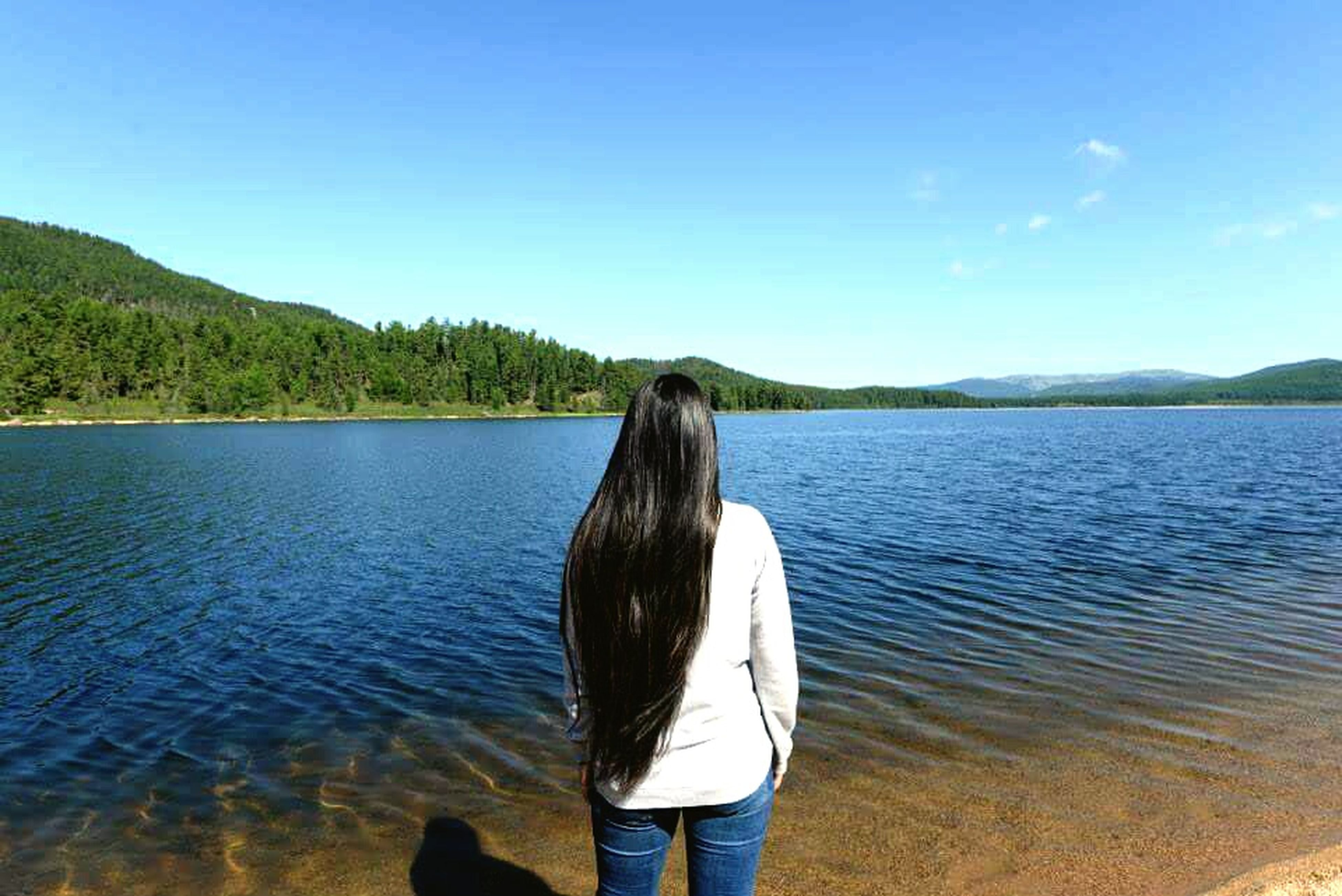 water, tranquility, lake, tranquil scene, rear view, scenics, mountain, lifestyles, beauty in nature, leisure activity, standing, nature, sky, clear sky, person, blue, long hair, idyllic