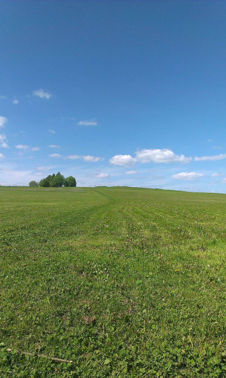 View Of Green Field Against Cloudy Sky