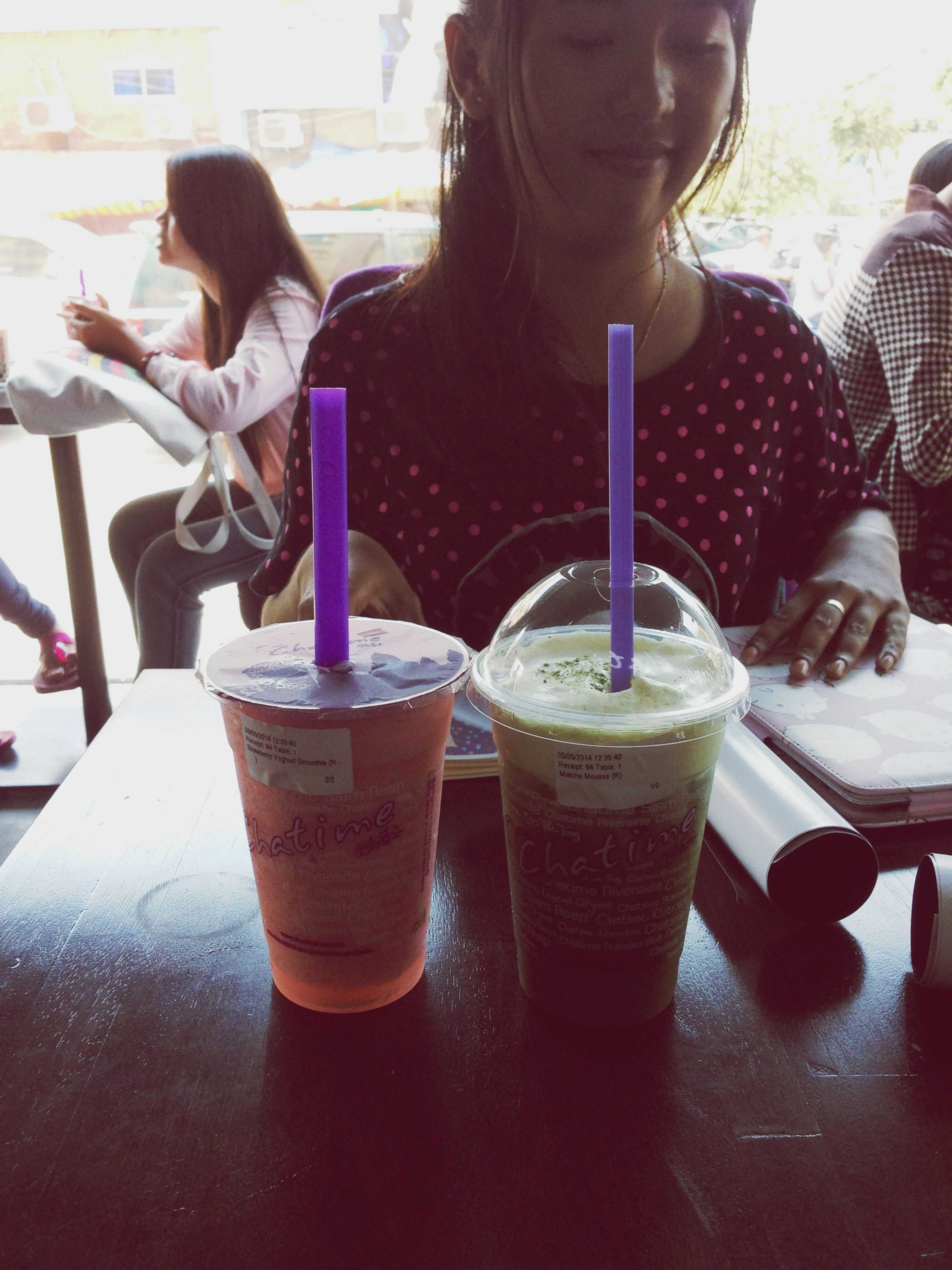 food and drink, drink, refreshment, table, freshness, lifestyles, drinking glass, leisure activity, indoors, coffee - drink, restaurant, drinking straw, coffee cup, person, holding, focus on foreground, incidental people, close-up