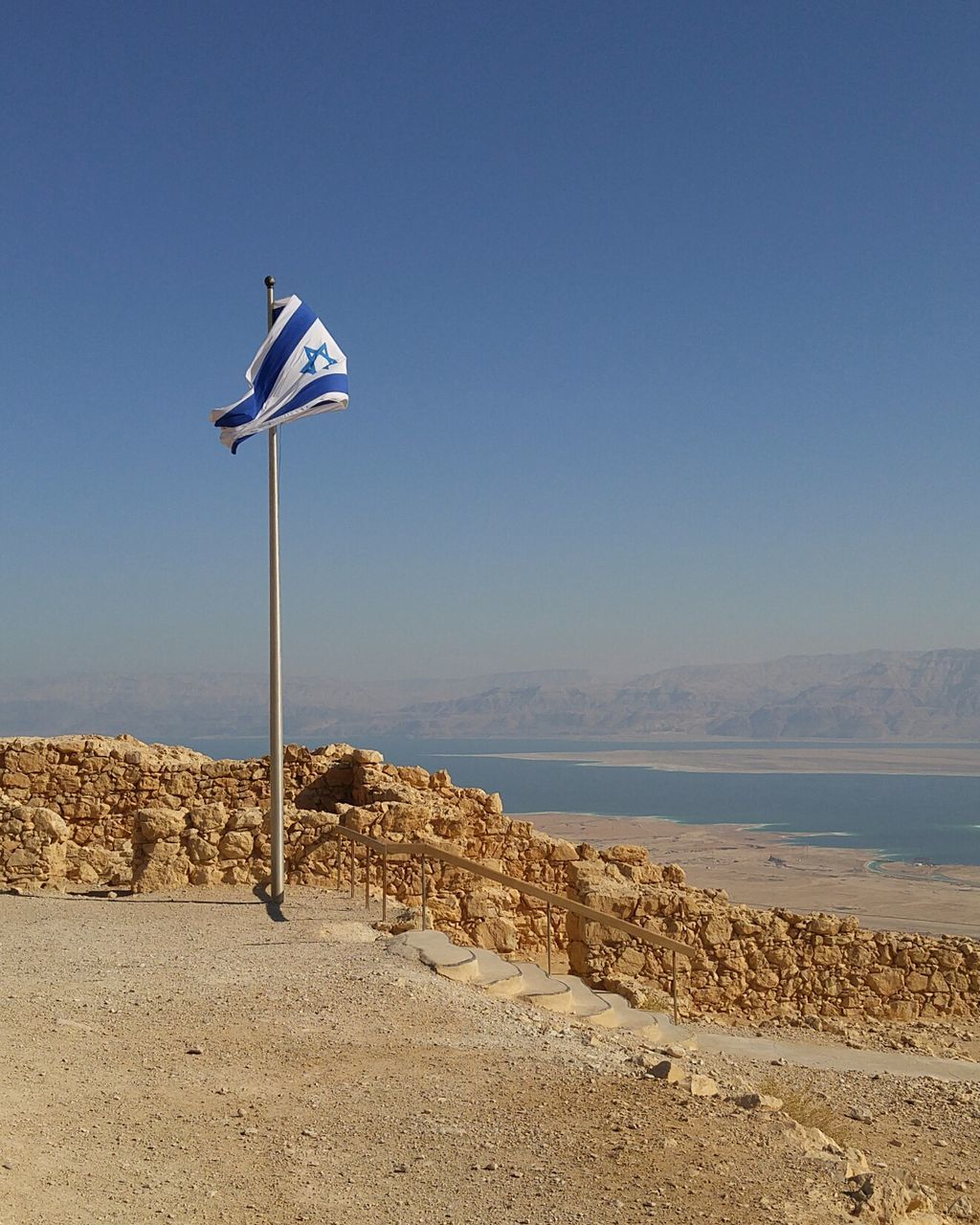 Israeli Flag By Lake Against Clear Blue Sky
