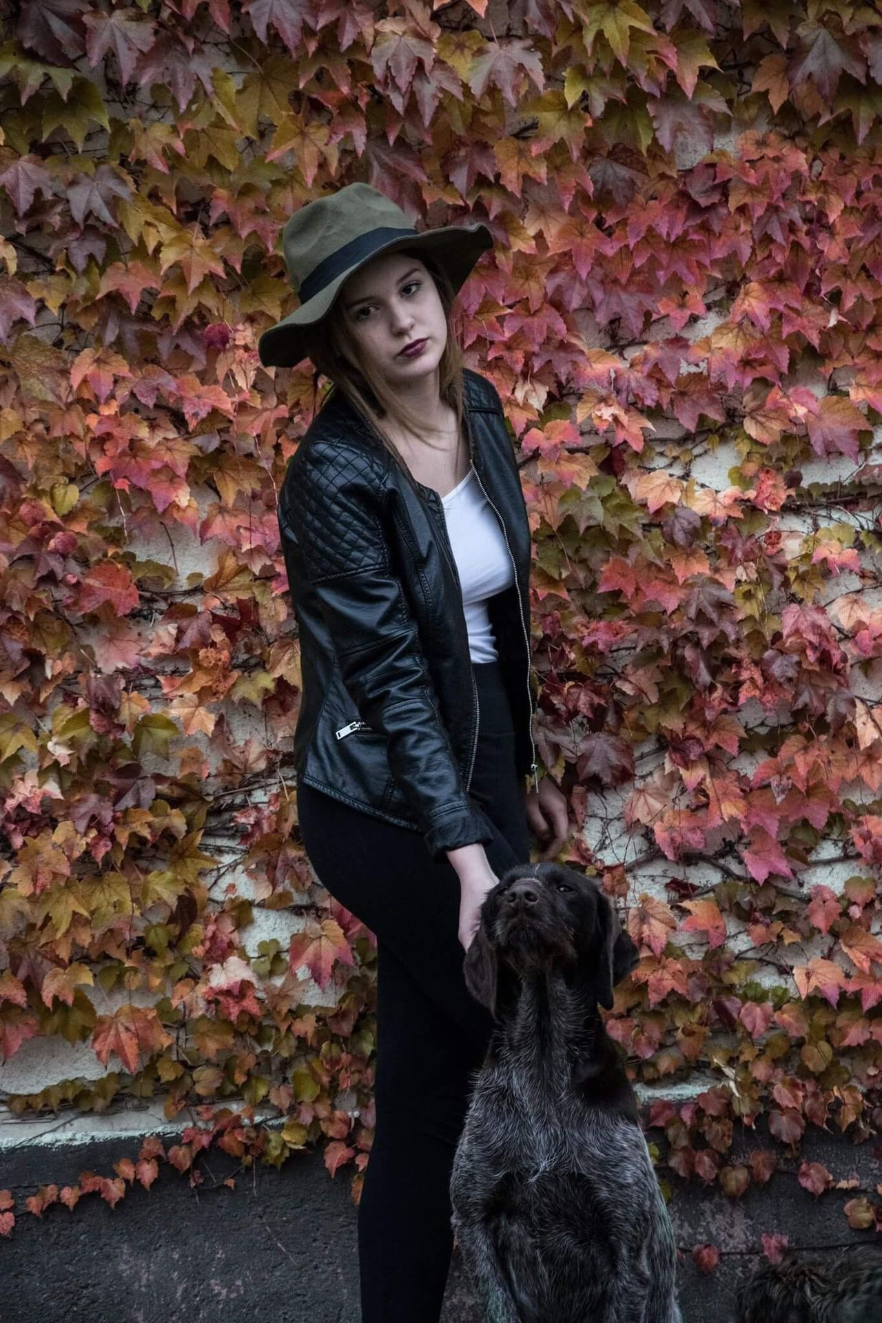 Sister & puppy Dog One Person Full Length Standing Brick Wall Pets Real People Overcoat One Animal Leaf Leisure Activity Young Adult Young Women Outdoors Day One Woman Only Mammal Adults Only Adult