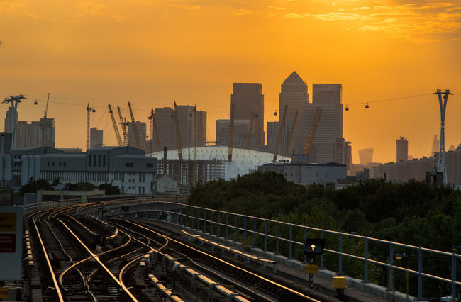 A Bird's Eye View Architecture Built Structure Cable Car Canary Wharf City Golden Golden Hour No People O2 Arena Orange Color Rail Transportation Railroad Station Railroad Track Railway Railway Track Romantic Sky Skyscraper Sunset The Magic Mission Train Track Transportation Urban Skyline London Lifestyle
