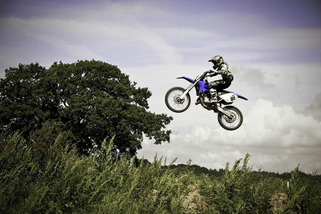 motorcycle, motocross, extreme sports, adventure, helmet, stunt, motorsport, danger, mid-air, risk, men, crash helmet, off-road vehicle, headwear, protective sportswear, speed, sports helmet, tree, jumping, real people, sports race, outdoors, sports clothing, riding, transportation, sport, motorcycle racing, day, field, sky, cloud - sky, one person, skill, competition, landscape, competitive sport, full length, sports track, biker, nature, people