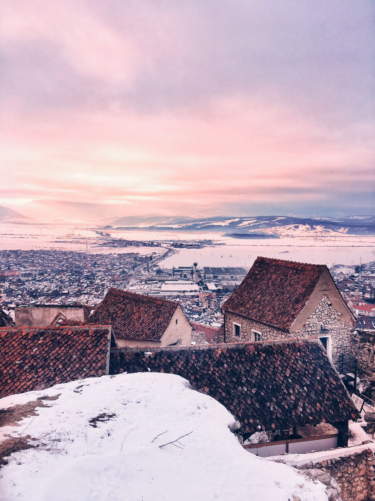 Winter sunset over the mountains in Rasnov Romania Snow Roof Winter House Citadel Medieval High Angle View Cold Temperature No People Sunset Nature Tiled Roof  Beauty In Nature Cityscape Outdoors