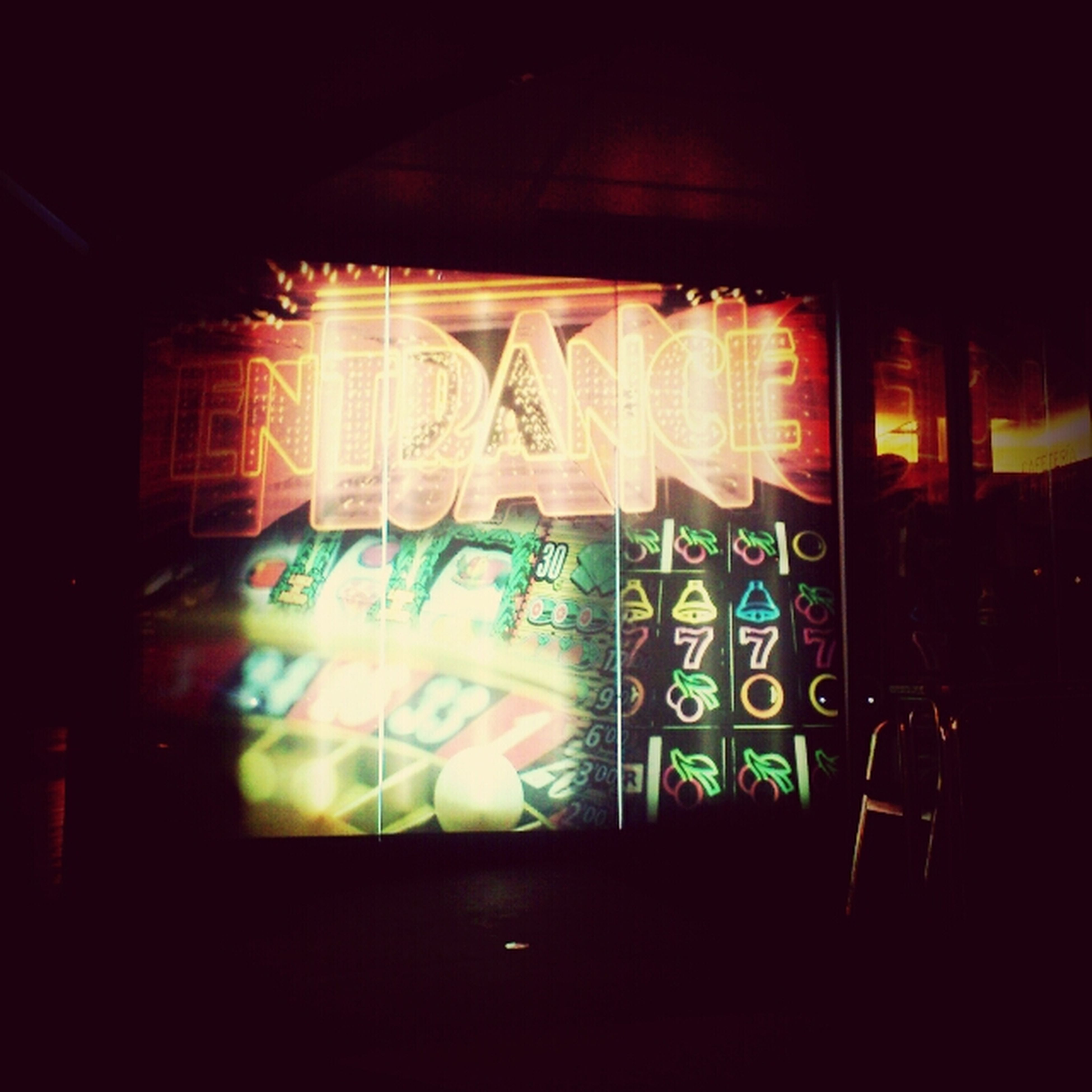 indoors, art, graffiti, illuminated, art and craft, creativity, multi colored, window, text, wall - building feature, built structure, dark, human representation, glass - material, no people, interior, architecture, night, western script, design