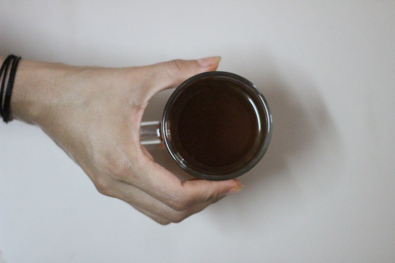 human hand, drink, human body part, holding, food and drink, one person, refreshment, human finger, real people, coffee cup, coffee - drink, directly above, freshness, indoors, close-up, men, white background, studio shot, food, day, people