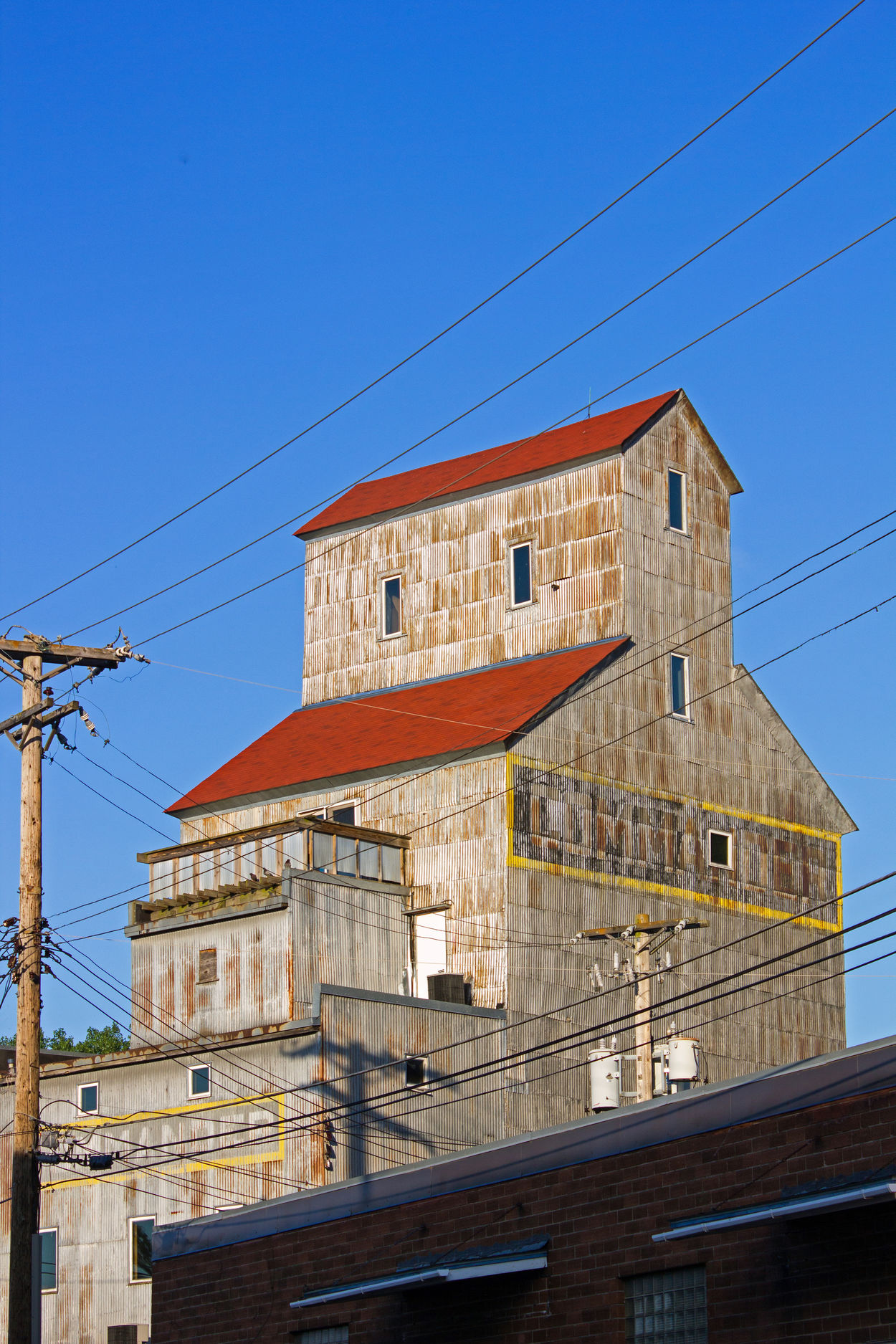 Commander grain elevator in Stillwater, Minnesota Architecture Blue Building Exterior Built Structure Cable Clear Sky Connection Day Electricity  Electricity Pylon Low Angle View No People Old Grain Elevator Outdoors Power Line  Power Supply Red Roof On Grain Elevator Sky Technology Telephone Line