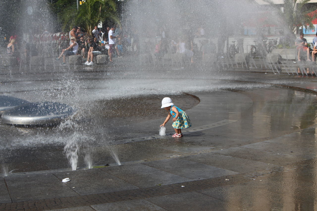water, spraying, real people, wet, splashing, motion, outdoors, lifestyles, day, full length, architecture, men, building exterior, city, one person, people, adult