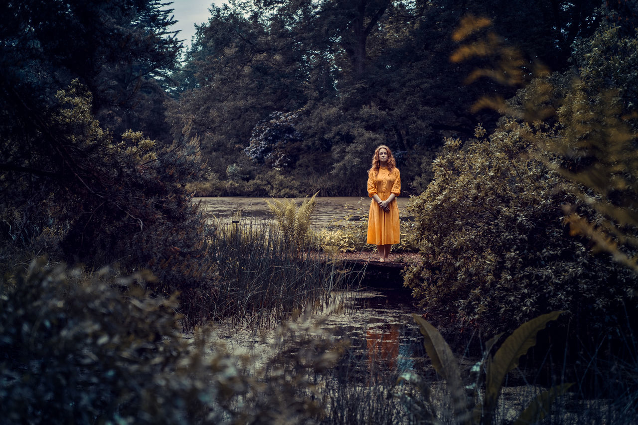 Yellow dressed young woman in the distance alone at a silent lake Adult Adults Only Beautiful Woman Beauty Beauty In Nature Day Fashion Field Forest Growth Lifestyles Looking At Camera Nature One Person One Woman Only One Young Woman Only Outdoors People Portrait Real People Standing Tree Women Young Adult Young Women