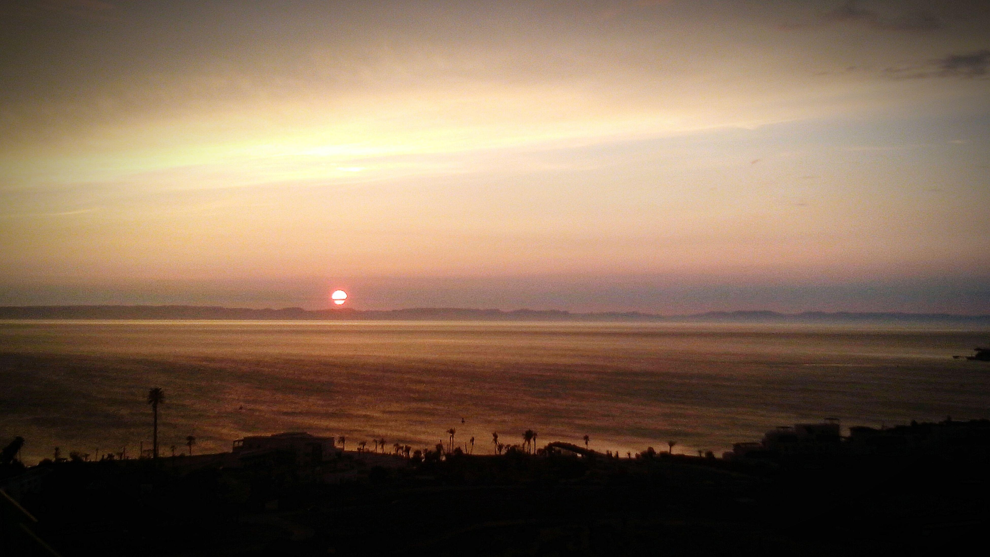 sunset, tranquil scene, tranquility, scenics, silhouette, beauty in nature, sky, landscape, sun, nature, water, idyllic, field, dusk, orange color, dark, sea, outdoors, non-urban scene, remote
