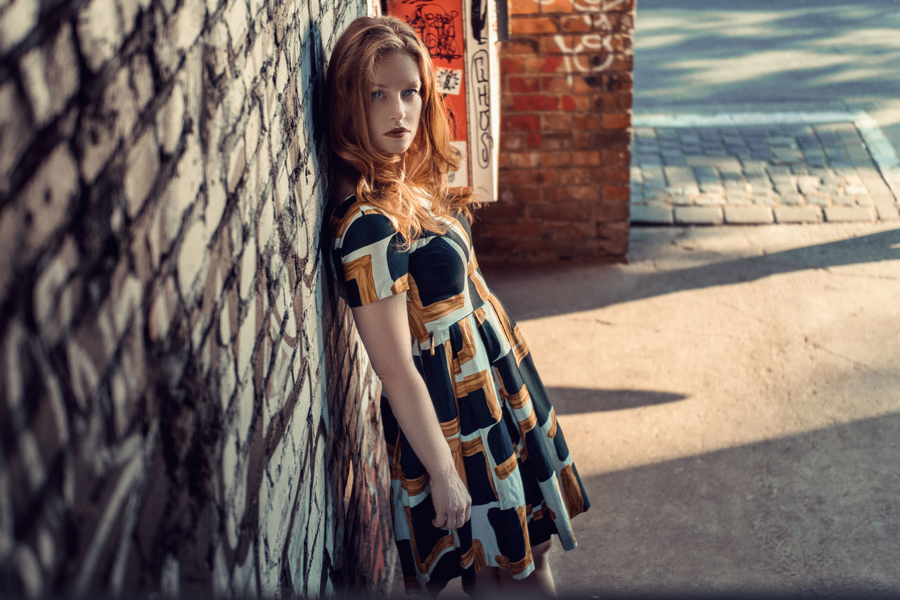Young woman standing at an old brick wall Adult Beautiful Woman Beauty Blond Hair Casual Clothing Day Looking At Camera One Person One Young Woman Only Outdoors People Portrait Real People Standing Young Adult Young Women