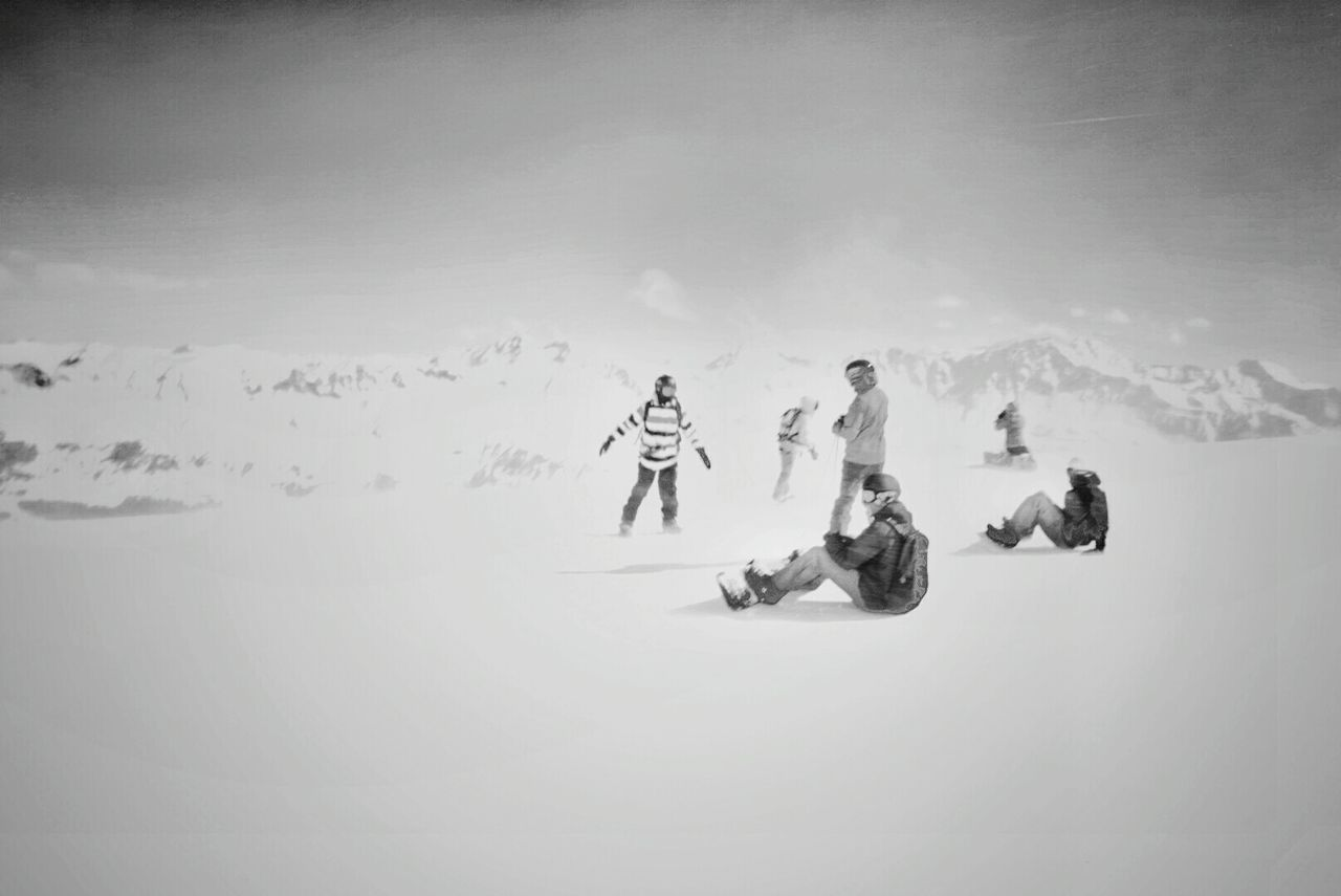 People Skiing On Snow Covered Field Against Sky