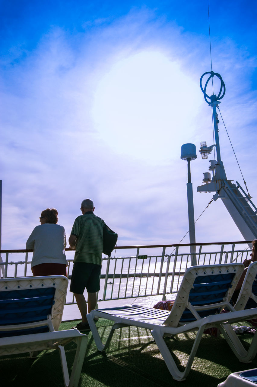 full length, sky, real people, two people, rear view, railing, outdoors, cloud - sky, men, day, leisure activity, togetherness, nautical vessel, nature, people