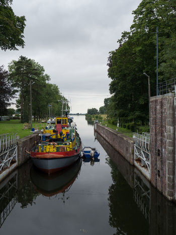 Beauty In Nature Boat Canal Cloud Cloud - Sky Cloudy Growth Idyllic Mode Of Transport Nature Nautical Vessel No People Outdoors Poland Pomorskie Przegalina Reflection Sky Standing Water Tourism Tranquil Scene Tranquility Travel Destinations Tree Water