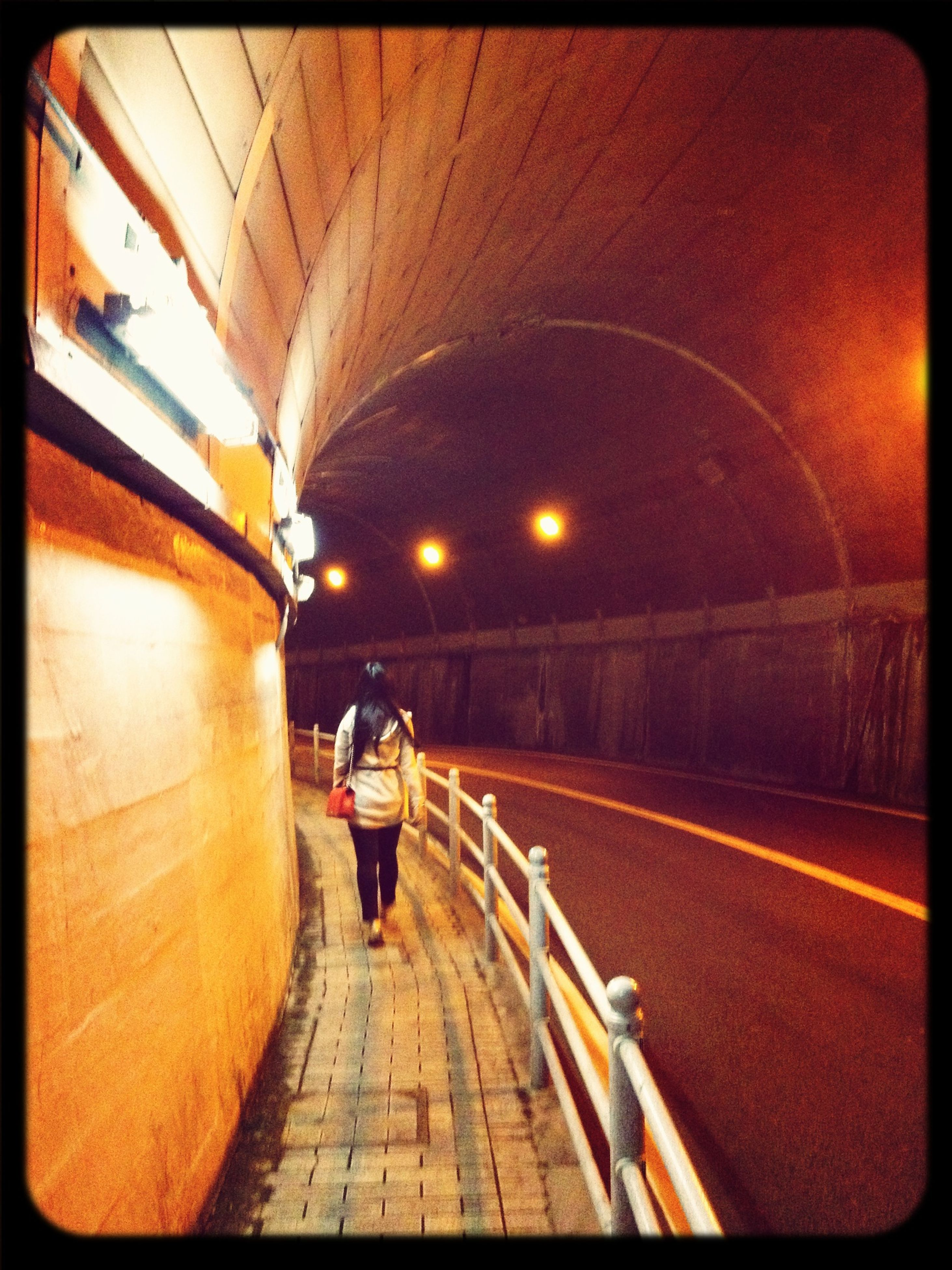 transfer print, lifestyles, rear view, auto post production filter, full length, walking, the way forward, men, leisure activity, transportation, illuminated, person, architecture, street, umbrella, built structure, tunnel, diminishing perspective