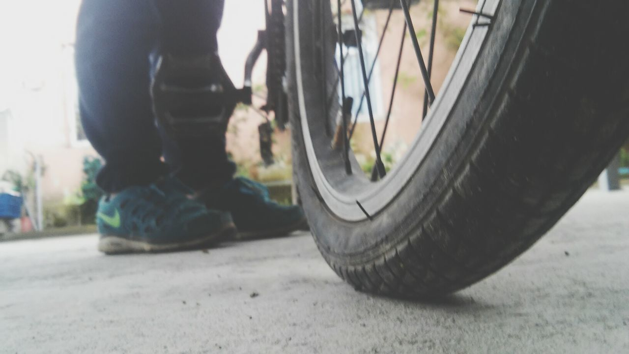 low section, transportation, wheel, land vehicle, day, bicycle, mode of transport, real people, one person, men, human leg, tire, outdoors, close-up, human body part, people