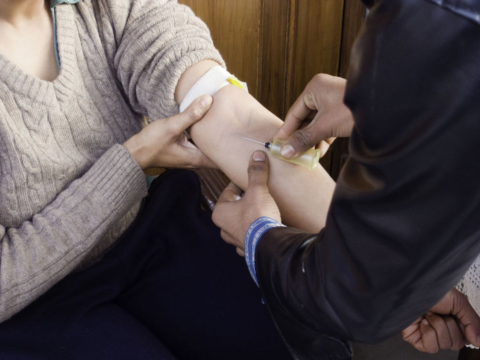 A lady getting a blood test, shown here with a syringe inserted into her hand. This is actually an empty tube into which the blood tube is inserted. The blood is taken by a technician who does a home visit. Adults Only Blood Test Hand Health Human Body Part Human Hand Medical Medical Test People Syringe Taking Blood Two People