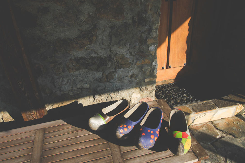 Two pair of clogs on a table, council of Gozon, Asturias, Spain. Architecture Asturias Clogs Country Life Day Door Footwear Outdoors Painted Rural Rural Life Shadow Shoe Stone Material Sunlight Sunny Typical Typical Spanish Wall - Building Feature Wooden