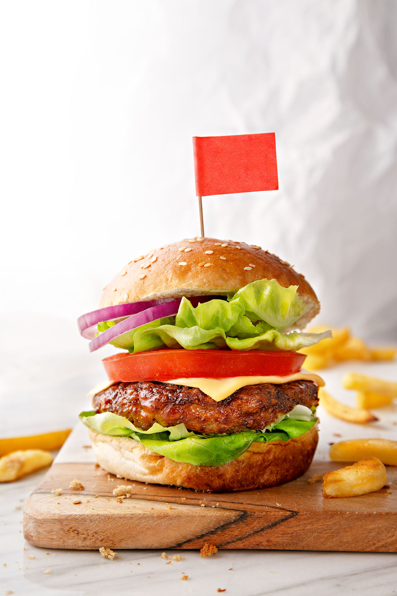 Tasty hamburger with french fries on a wooden board Bread Bun Close-up Fast Food Food Food And Drink Freshness Hamburger Indoors  Lettuce Meal Meat No People Ready-to-eat Sandwich Sesame Snack Studio Shot Take Out Food Tomato Unhealthy Eating