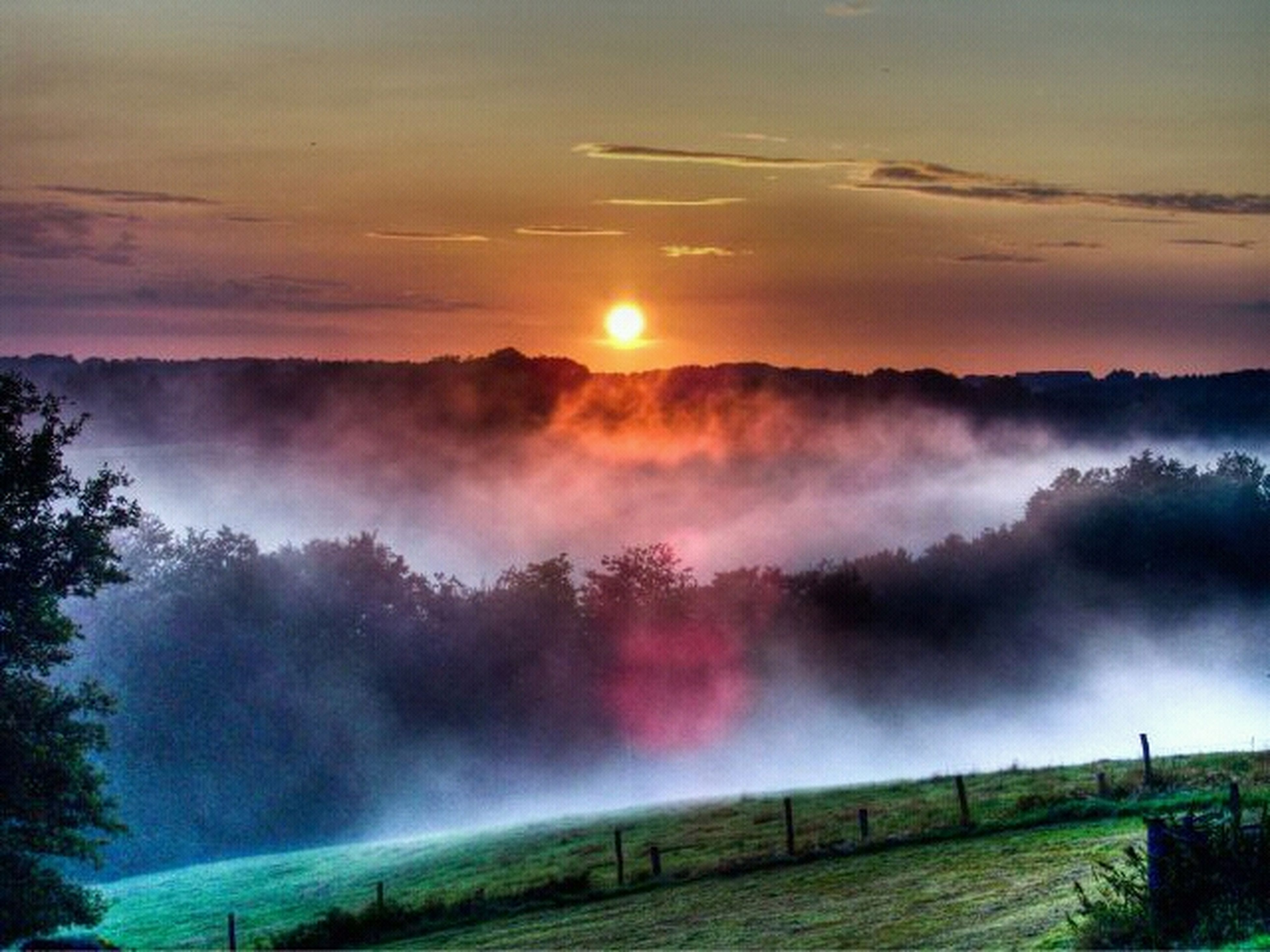 scenics, tranquil scene, sunset, beauty in nature, tranquility, landscape, fog, nature, sky, idyllic, weather, mountain, sun, foggy, field, cloud - sky, non-urban scene, orange color, sunbeam, rural scene