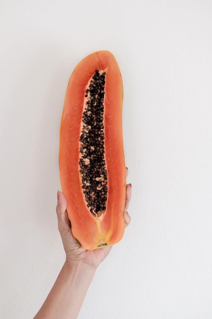 Cropped Image Of Woman Holding Halved Papaya Over White Background