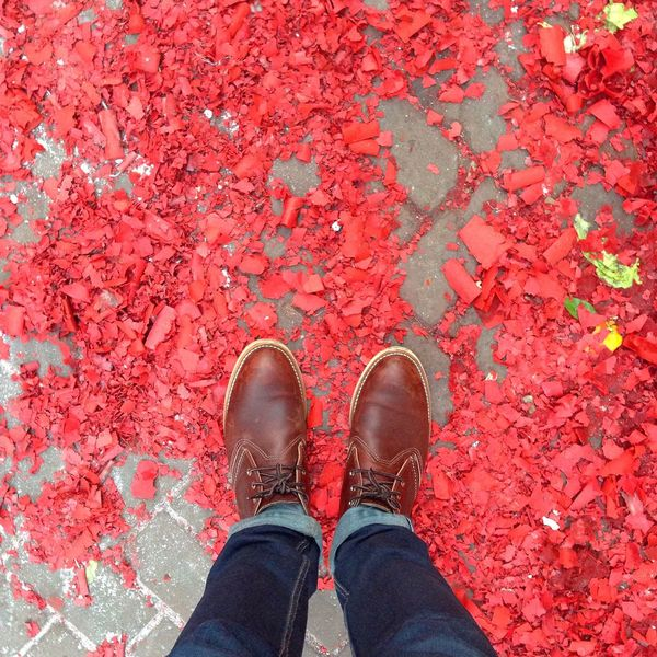 Chinese New Year aftermath Chinese Culture Chinese New Year Redwing Boots Red Confetti Celebration Street Cobblestone Streets Feet Denim Jeans Walking Europe Travel