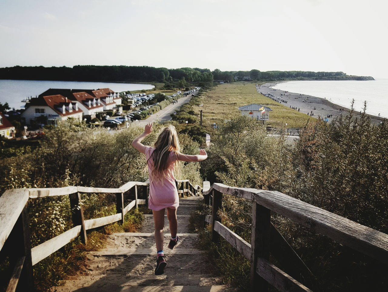 Rear View Of Girl Walking On Footpath Leading Towards Beach