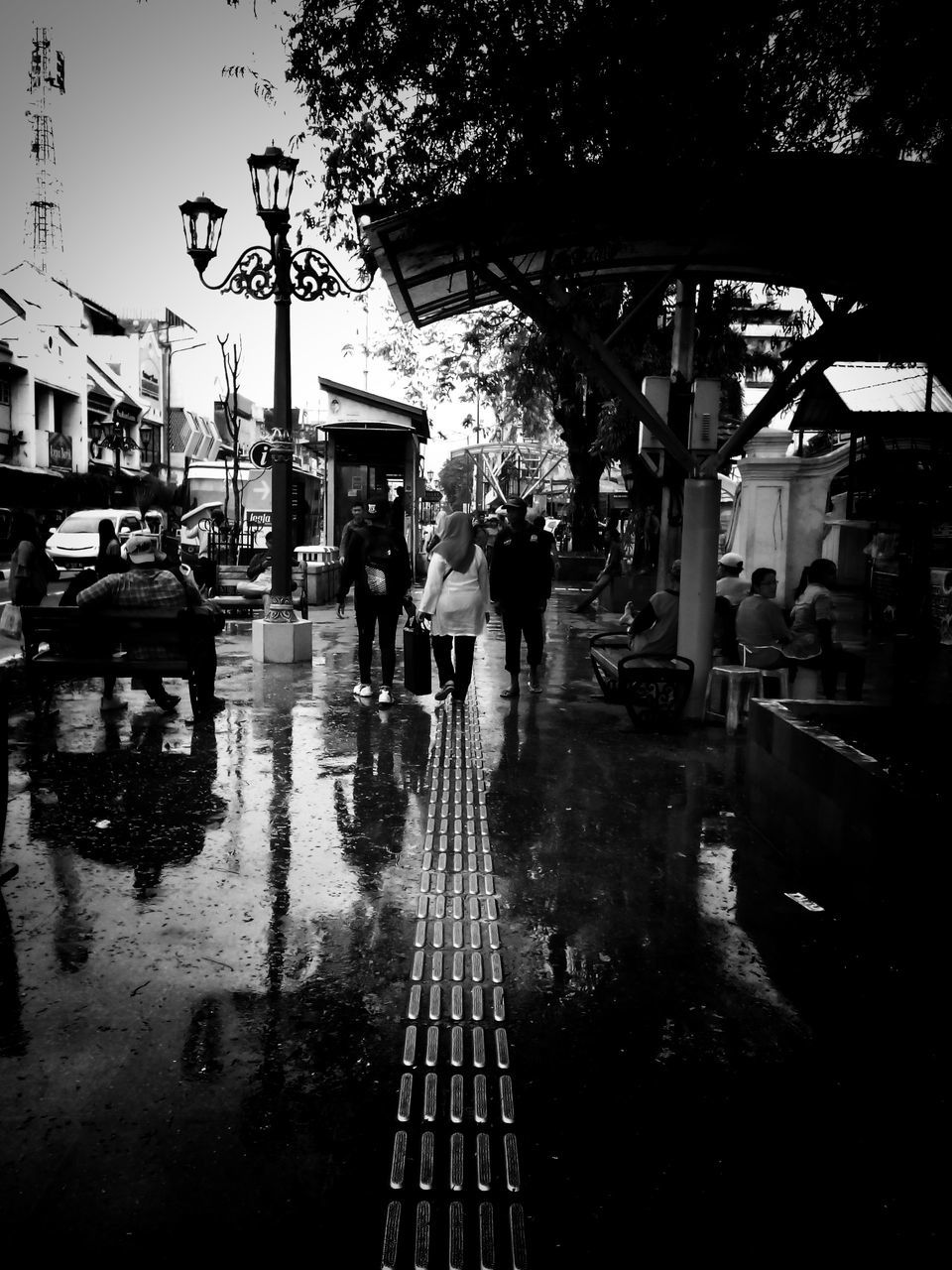 wet, street, real people, water, building exterior, rainy season, architecture, built structure, outdoors, city life, walking, city, transportation, day, lifestyles, road, men, women, one person, people