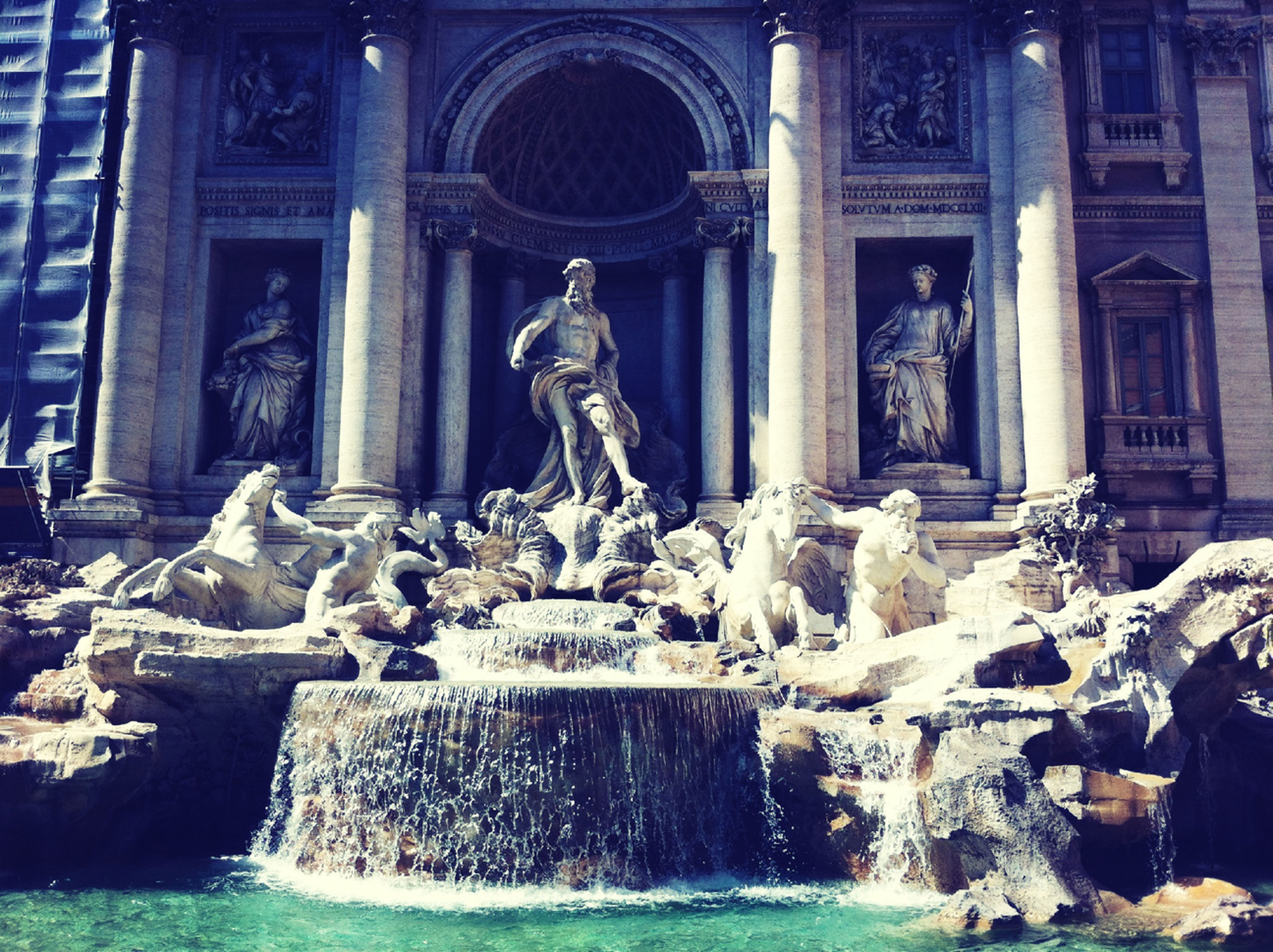 architecture, water, built structure, statue, building exterior, fountain, sculpture, art and craft, human representation, art, architectural column, famous place, creativity, history, travel destinations, religion, splashing, spirituality, waterfront
