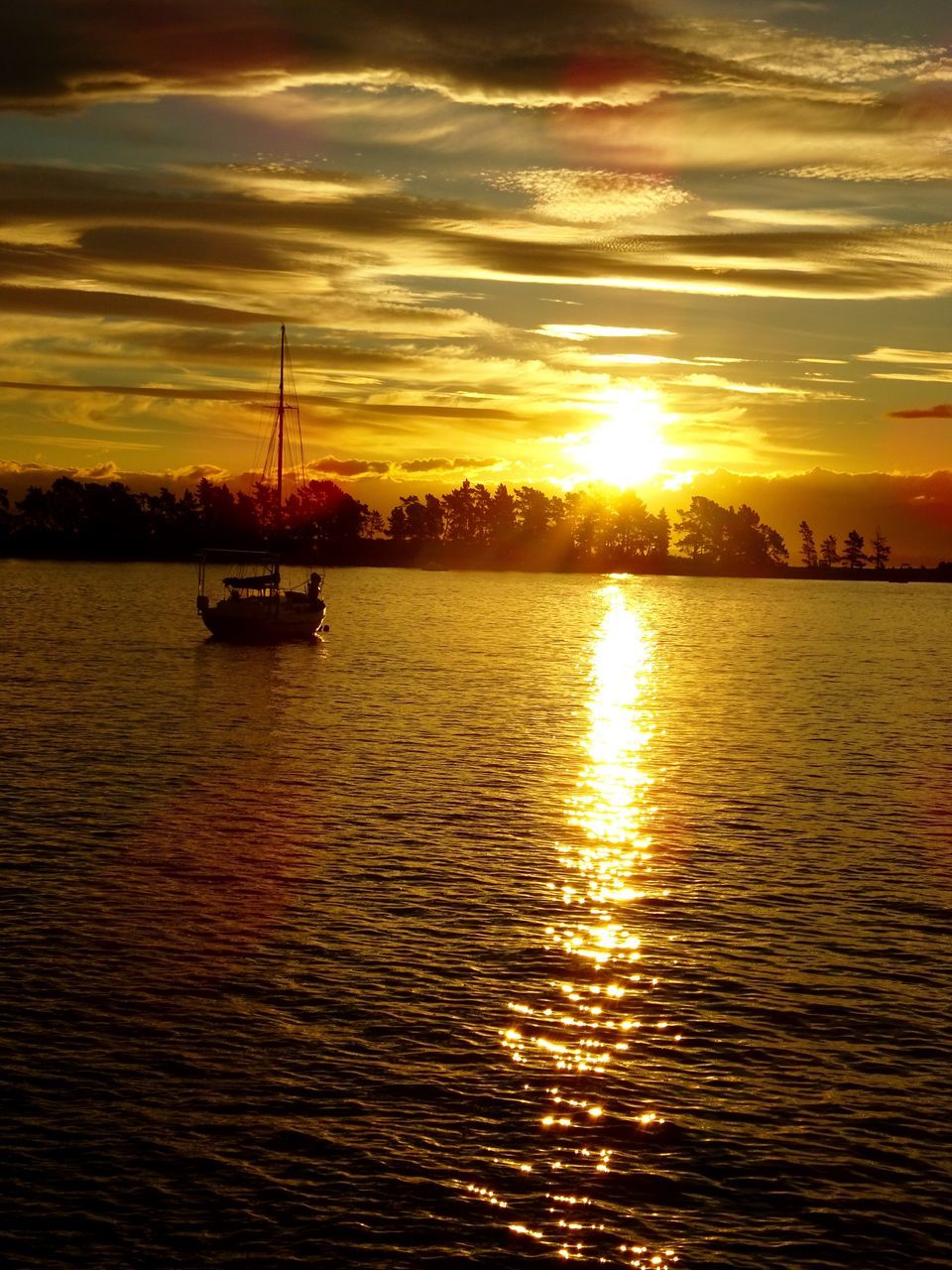 sunset, water, cloud - sky, sky, nautical vessel, orange color, waterfront, nature, beauty in nature, reflection, dramatic sky, silhouette, tranquility, scenics, tranquil scene, sea, transportation, mode of transport, sun, rippled, no people, outdoors, mast