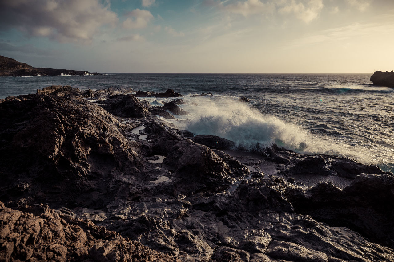A big wave splashes in the foreground on a rocky beach Beach Beauty In Nature Day Horizon Over Water Motion Nature No People Outdoors Power In Nature Rock - Object Scenics Sea Sky Tranquil Scene Tranquility Water Wave