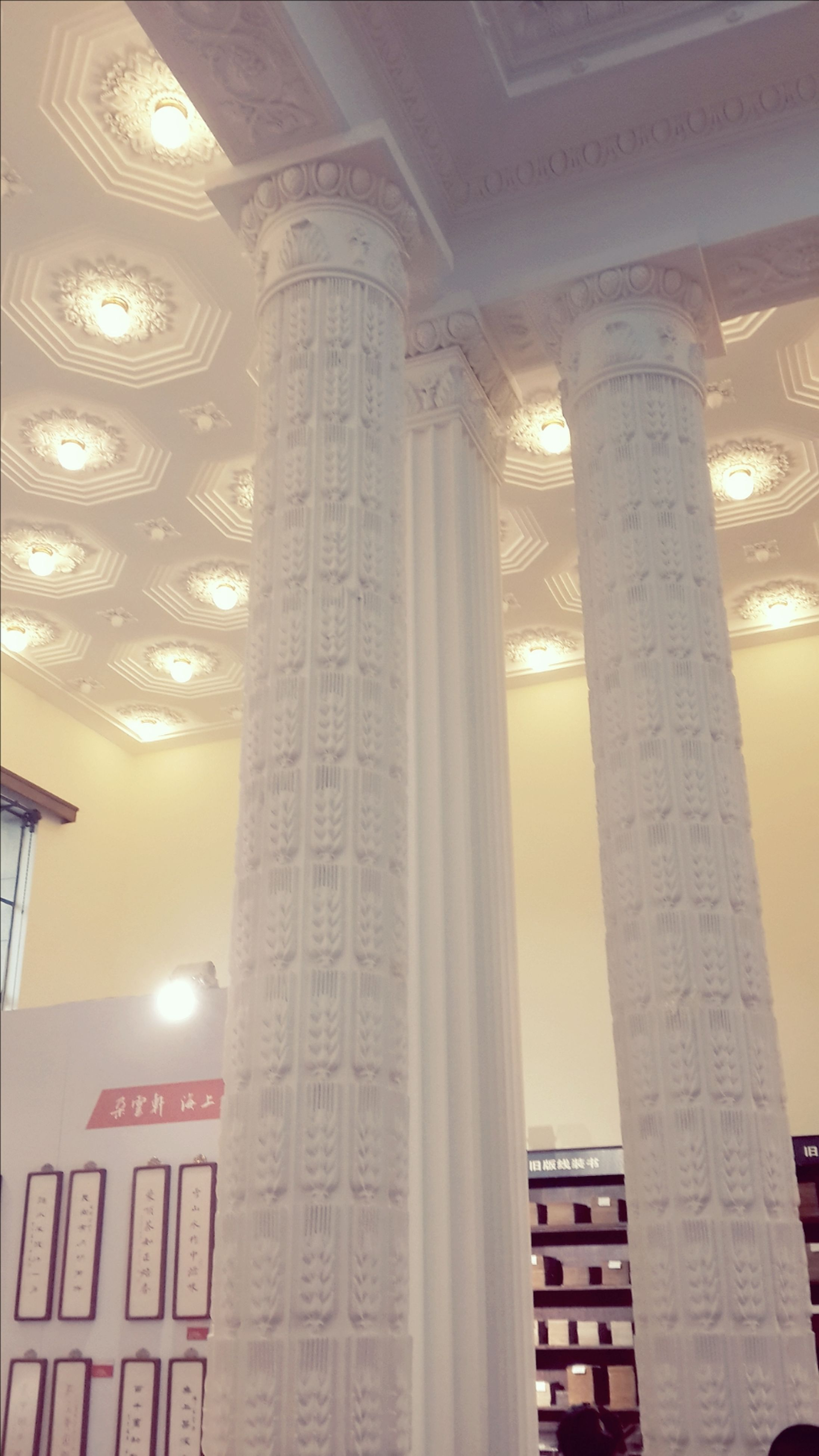 architecture, indoors, built structure, low angle view, architectural column, illuminated, ceiling, lighting equipment, religion, column, architectural feature, interior, history, building, building exterior, spirituality, no people, famous place, place of worship