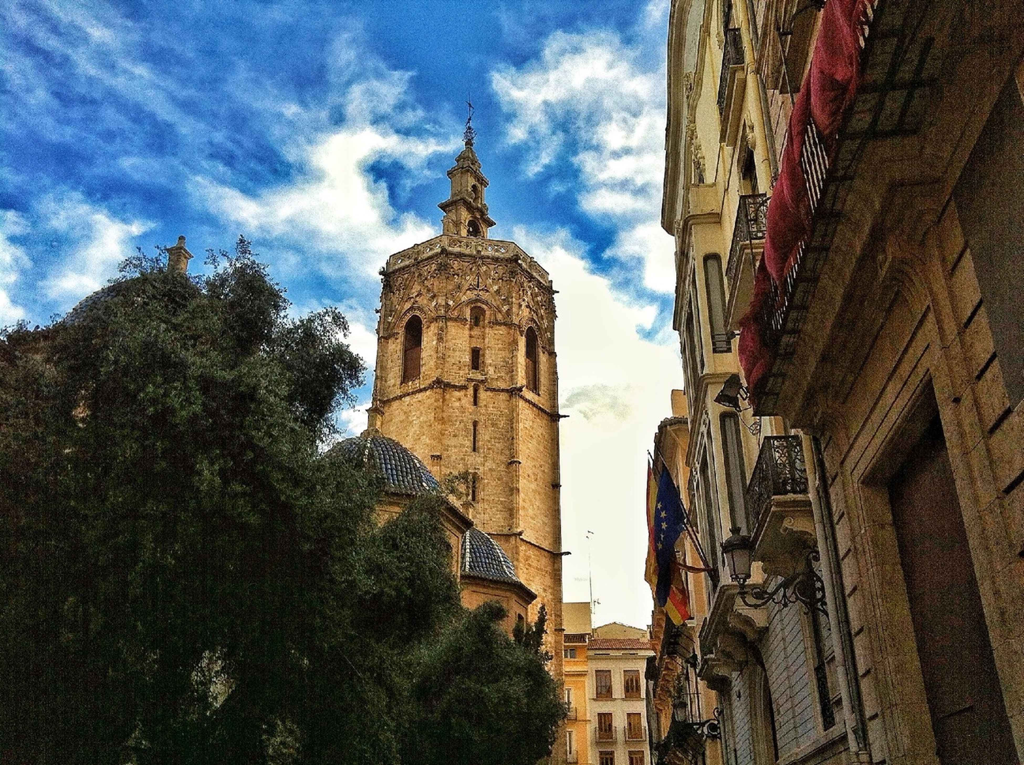 architecture, building exterior, built structure, low angle view, sky, tree, church, tower, religion, history, place of worship, cloud, cloud - sky, clock tower, spirituality, travel destinations, day, city, blue
