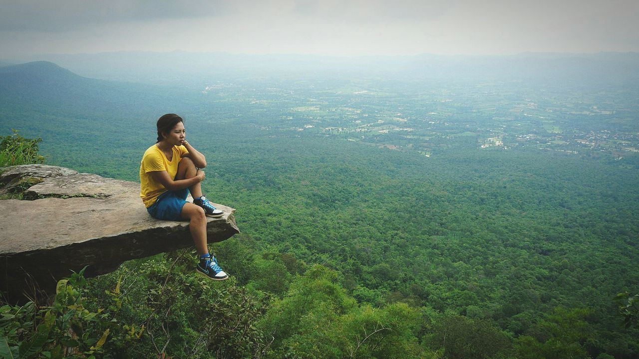 Woman Sitting On Top Of Mountain Over Forest