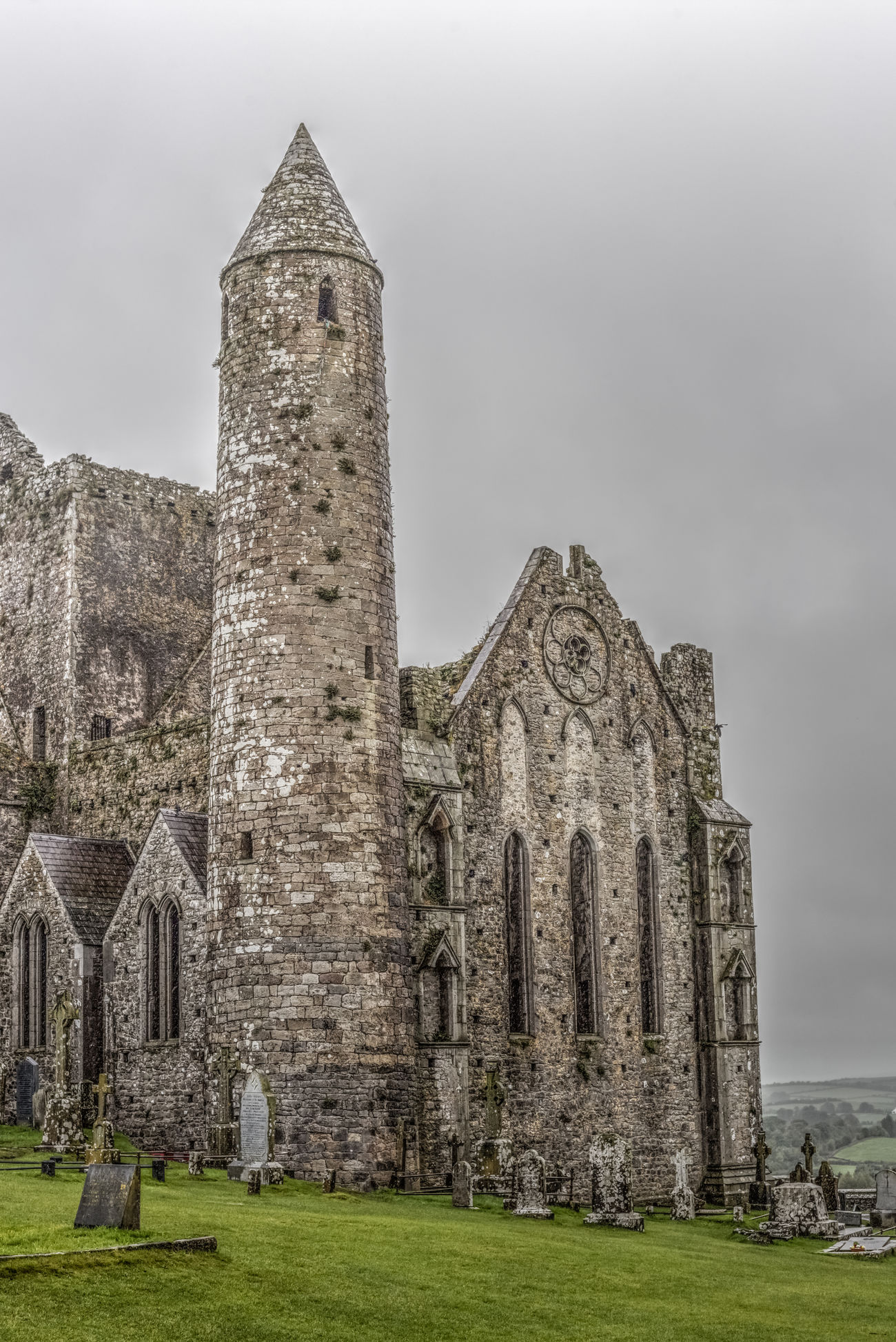 Rainy gloom descends over the Rock of Cashel, County Tipperary. The round tower dates from c.1100 while the cathedral was built between 1235 and 1270. The rock was sacked in 1647 during the Irish Confederate Wars by forces aligned with Cromwell. Close to 1,000 were killed during the sacking of Cashel, as many of the locals had sought protection in the church, with the bodies in the churchyard being described as being five or six deep. In the final stand numerous ladders were laid against the church windows and soldiers swarmed the building. For another half an hour the massacre raged on inside the church, until a depleted few retreated up the bell tower. Only sixty defending soldiers remained at this point, and accepted a final call to surrender. However, after they had descended the tower and thrown their swords away, all were killed. The atrocity at Cashel caused a deep impact in Ireland, as it was the worst single atrocity committed in Ireland since the start of fighting in 1641. The Rock of Cashel was finally abandoned completely in 1749 with the removal of the cathedral roof. Love Life, Love Photography Architecture Building Exterior Built Structure Day History Medieval Mountain No People Outdoors Travel Destinations Irish Catholic Cathedral Ruins Cromwell  Rock Of Cashel Old Buildings Medieval Architecture Tipperary Ireland Round Tower Church Stone Old Ruin Gloomy