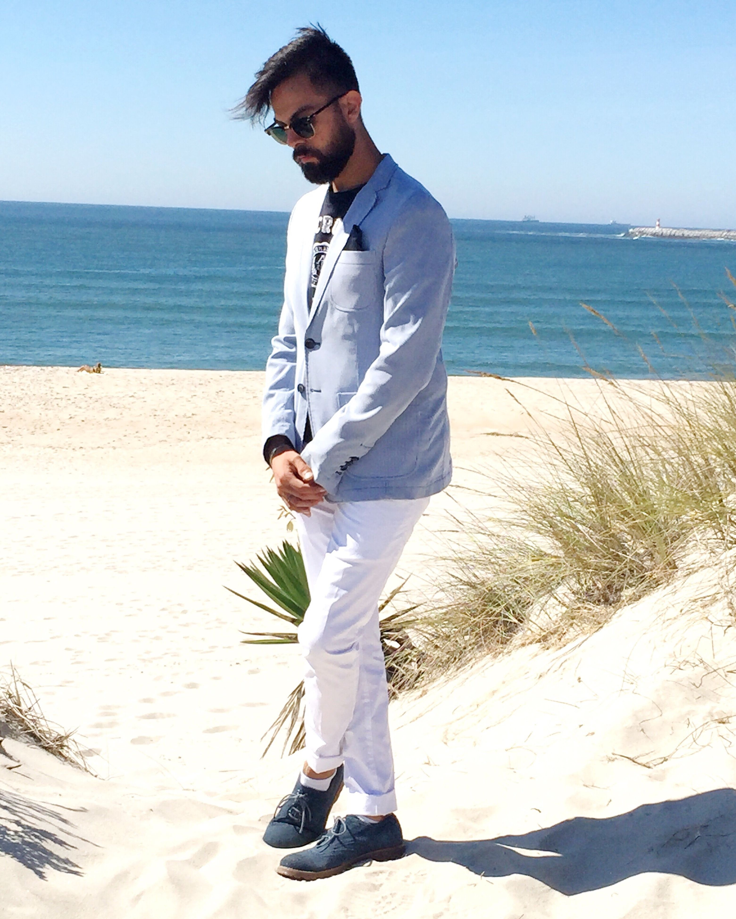 young adult, sand, full length, sunlight, beach, young men, shadow, sunglasses, casual clothing, sunny, water, person, clear sky, confidence, sea, outdoors, tranquil scene, tranquility, nature, beauty in nature, shore, day, scenics, sandy