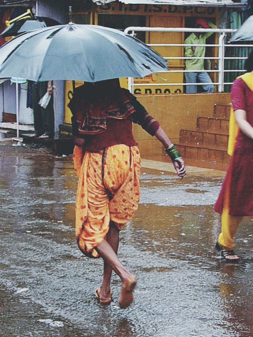 rain, rainy season, wet, water, weather, protection, walking, real people, street, outdoors, raindrop, two people, architecture, below, women, rear view, full length, lifestyles, men, built structure, under, leisure activity, day, togetherness, city, puddle, low section, adult, people