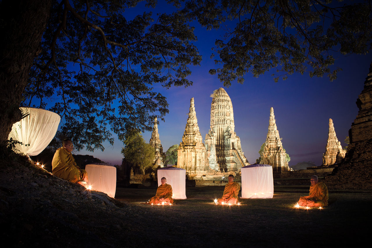 Monks light candles and pray to buddha statue in temple Architecture Building Exterior Built Structure Day Nature Outdoors Place Of Worship Religion Sky Spirituality Travel Destinations Tree