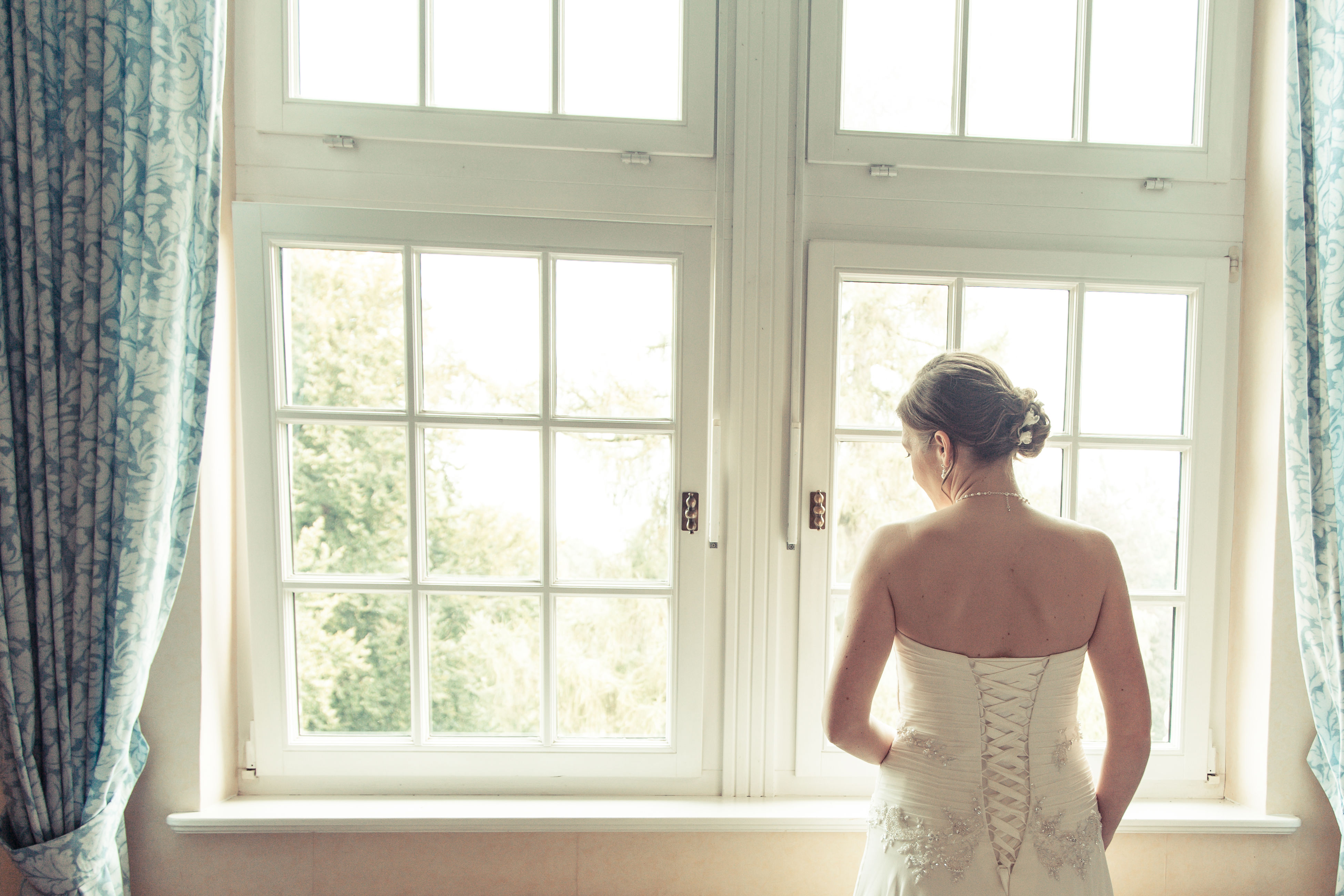 window, one person, indoors, standing, day, rear view, real people, looking through window, sunlight, young adult, beautiful woman, evening gown, wedding dress, one woman only, bride, adult, people, adults only