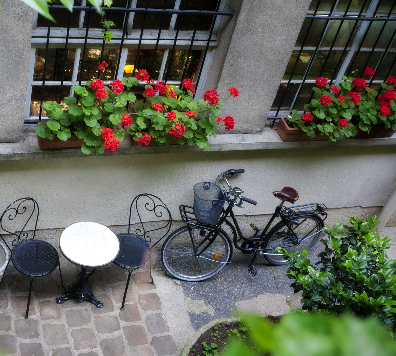 Courtyard in the Marais in Paris, France. Bicycle Bicycles Bike With Basket Cafe Seating Culture Flower Flower Pot Geraniums Paris Je T Aime Paris Scene Paris, France  Plant Potted Plant Red Flowers Wall - Building Feature Celebrate Your Ride