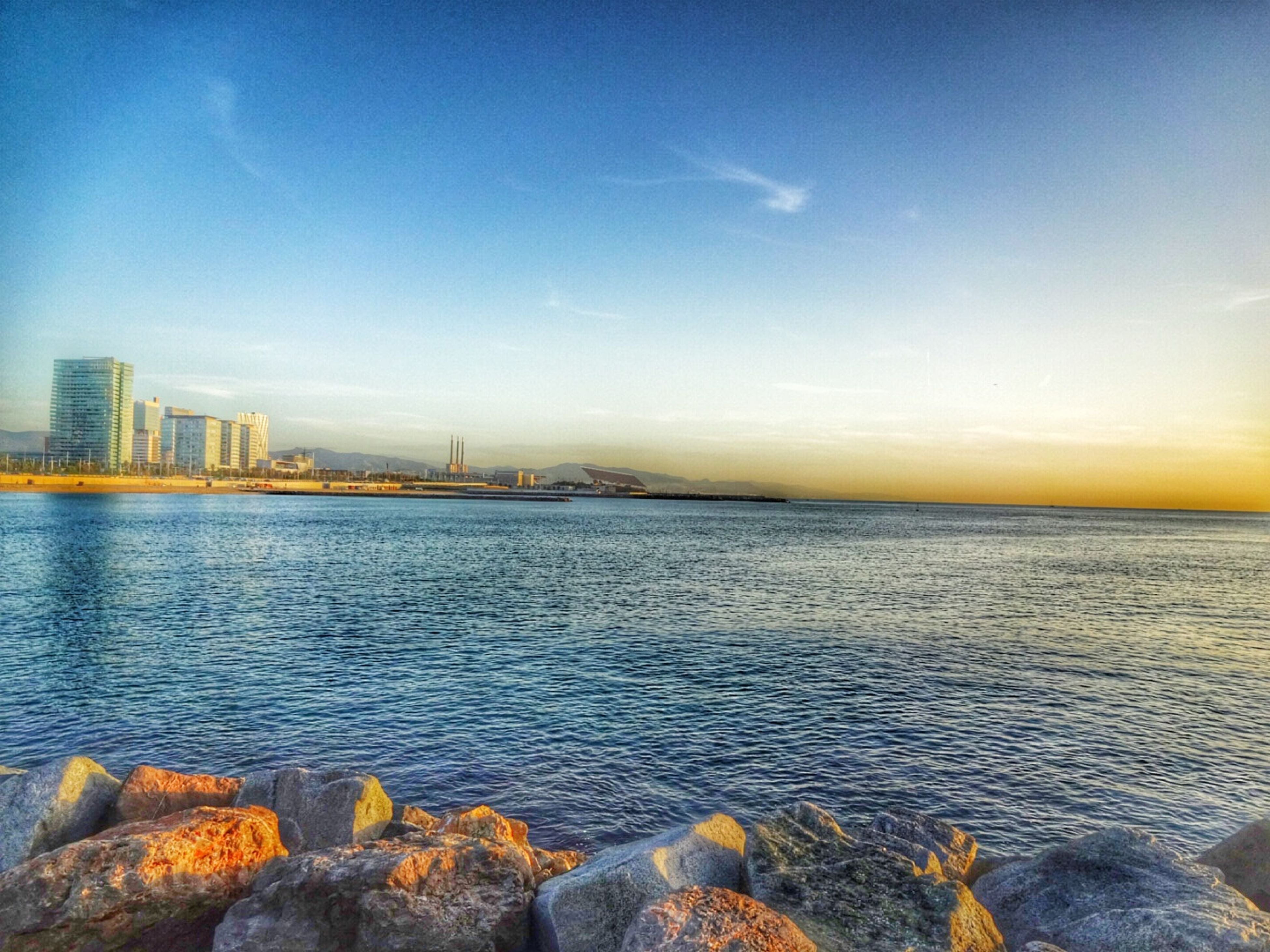 water, sea, building exterior, sky, architecture, built structure, city, scenics, waterfront, rippled, nature, beauty in nature, tranquil scene, sunset, tranquility, horizon over water, rock - object, cityscape, blue, river