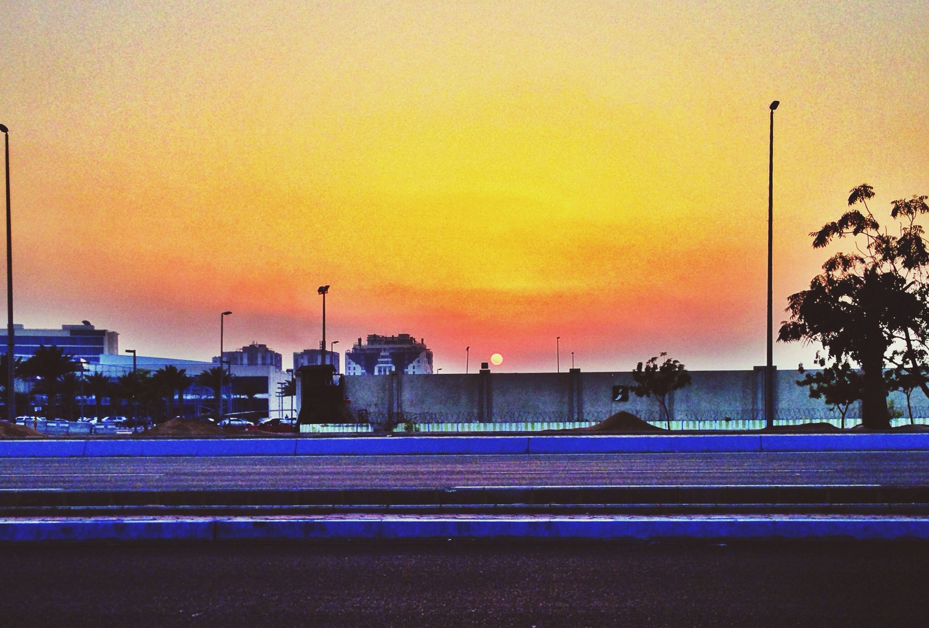 sunset, orange color, illuminated, architecture, built structure, sky, building exterior, street light, lighting equipment, transportation, dusk, motion, outdoors, light trail, city, no people, road, railing, clear sky, connection