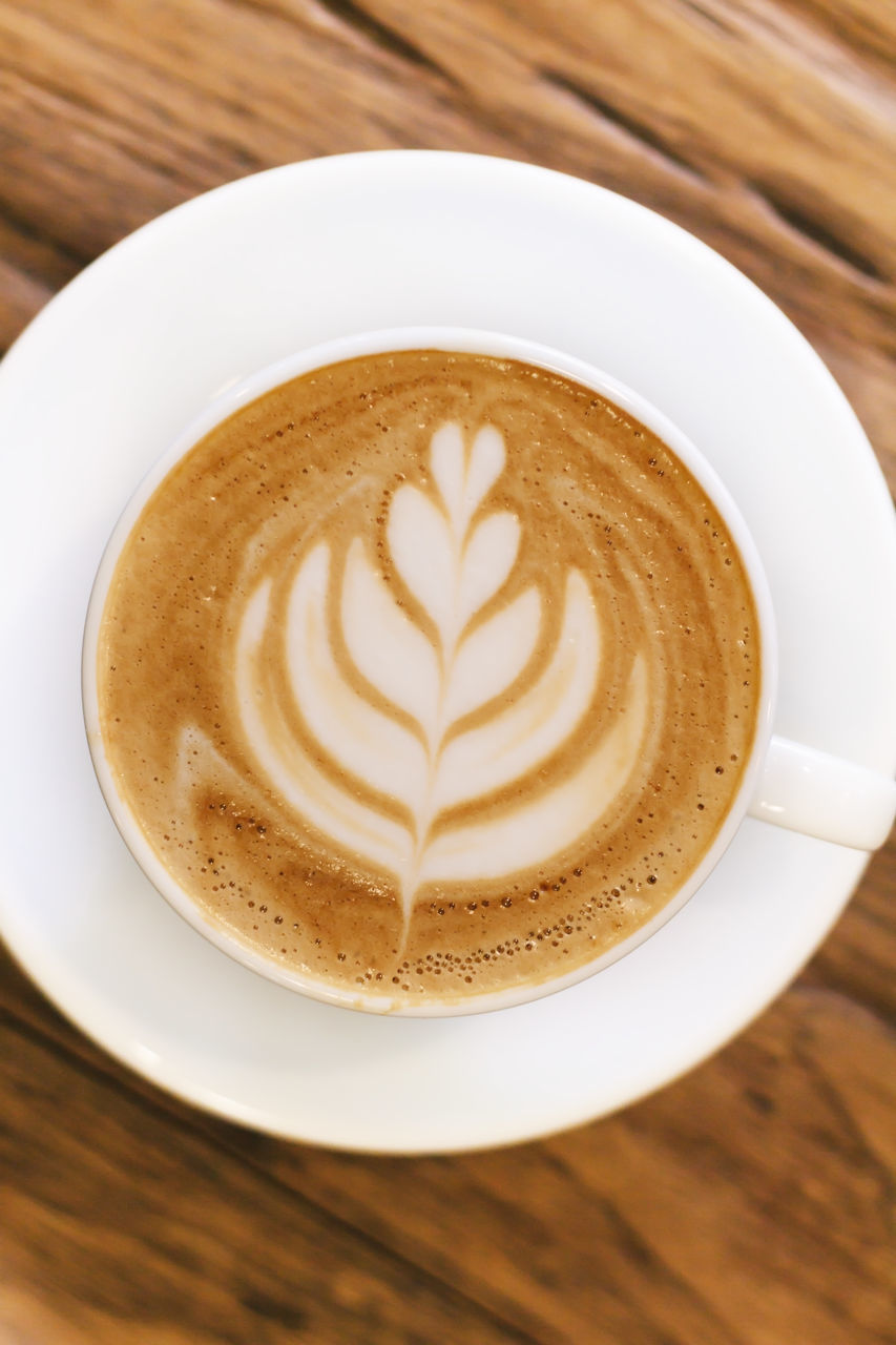 coffee cup, coffee - drink, frothy drink, table, froth art, drink, cappuccino, food and drink, refreshment, creativity, indoors, wood - material, latte, saucer, close-up, high angle view, freshness, no people, directly above, leaf, thick, day