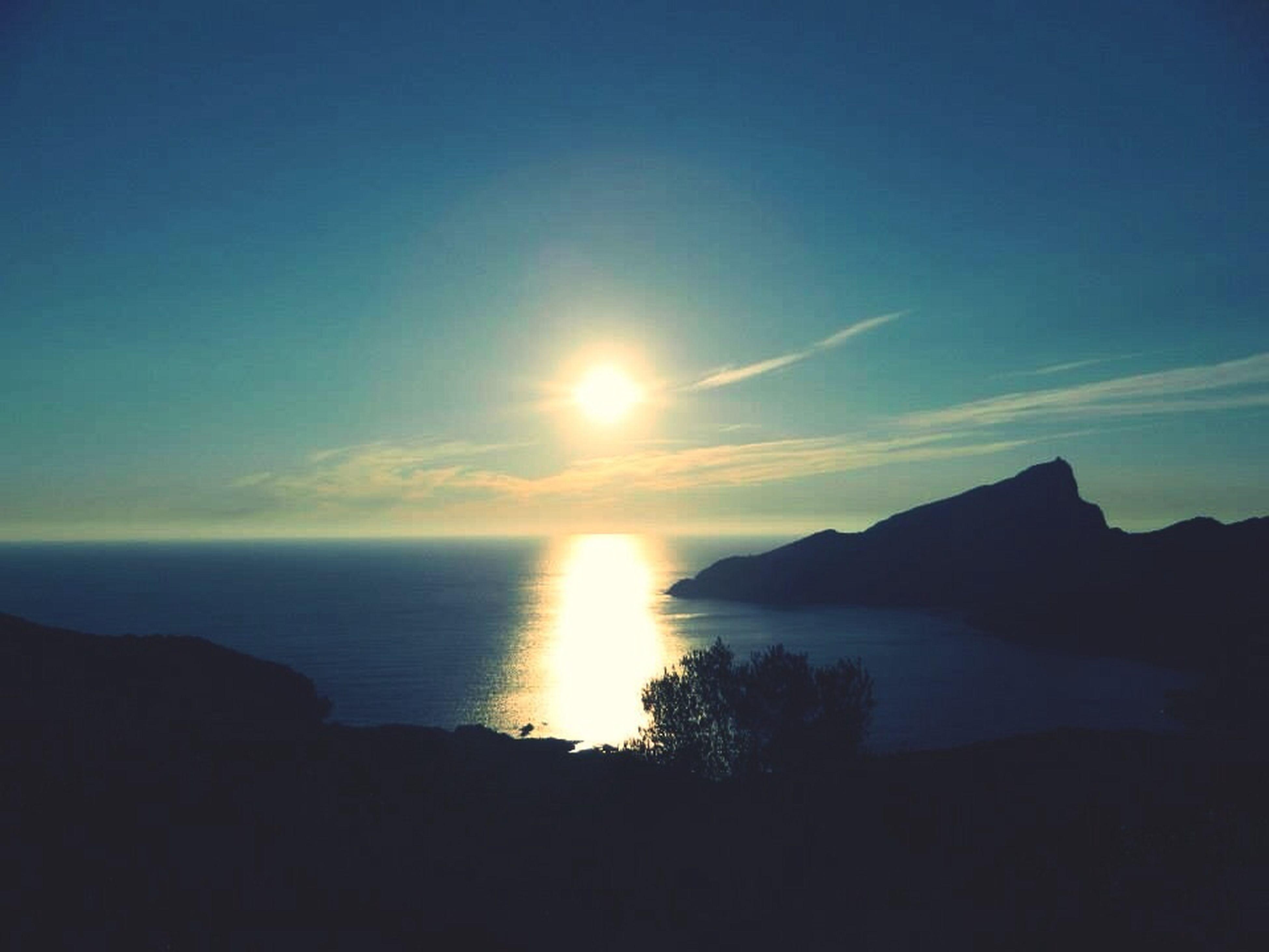tranquil scene, scenics, sea, water, sun, tranquility, beauty in nature, sky, silhouette, horizon over water, sunset, idyllic, nature, reflection, mountain, sunlight, sunbeam, blue, calm, outdoors